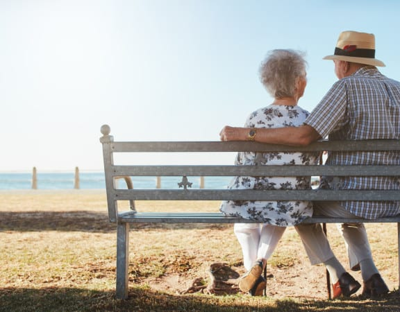 Rear view of loving senior couple relaxing at the seaside. Elderly man and woman sitting a bench outdoors.